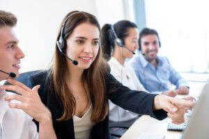 A call centre agent receiving help from a call centre team leader